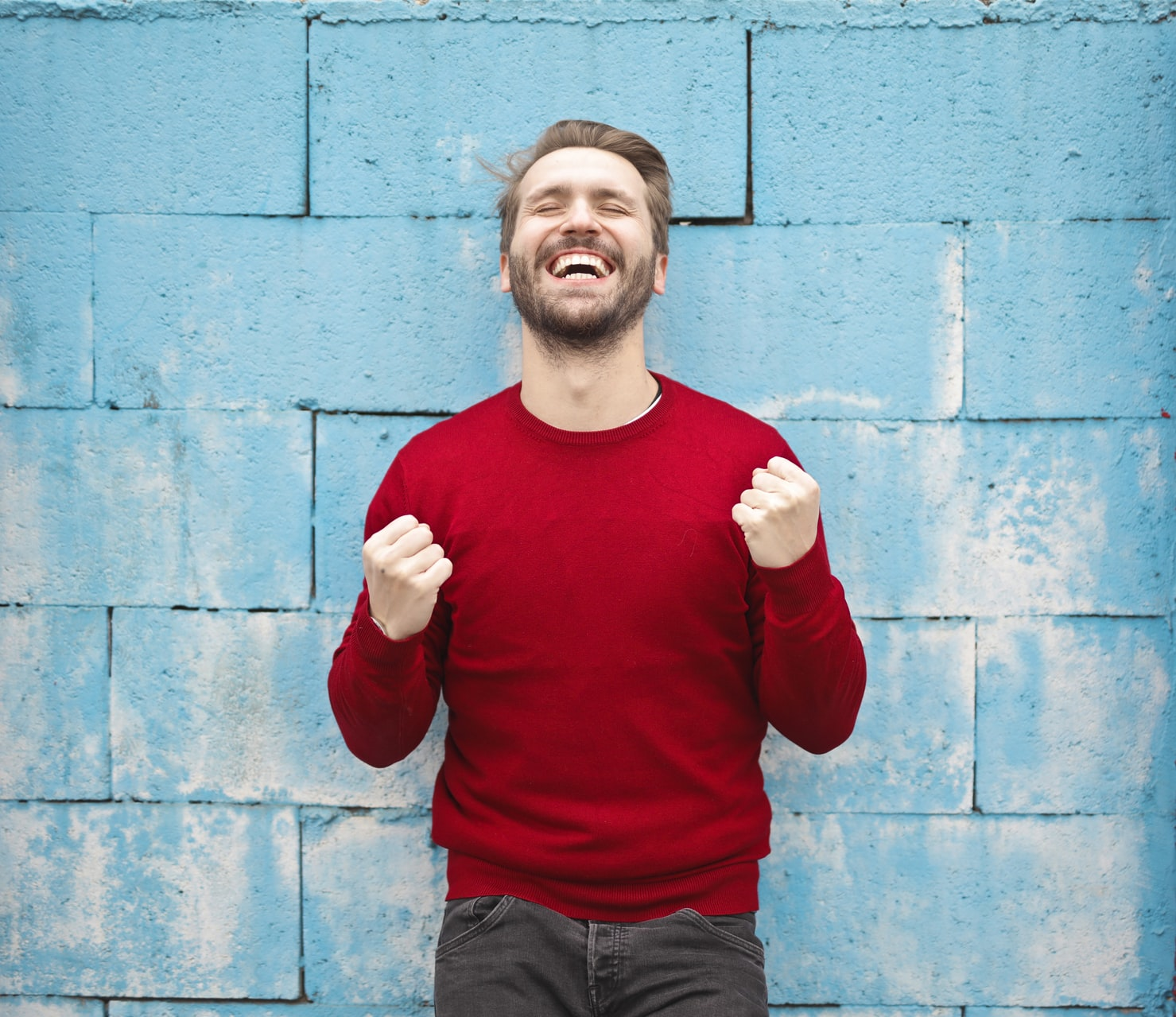 Man in a red sweater smiling in front of a blue wall