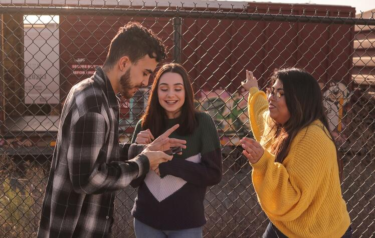 Teens talking in front of a fence